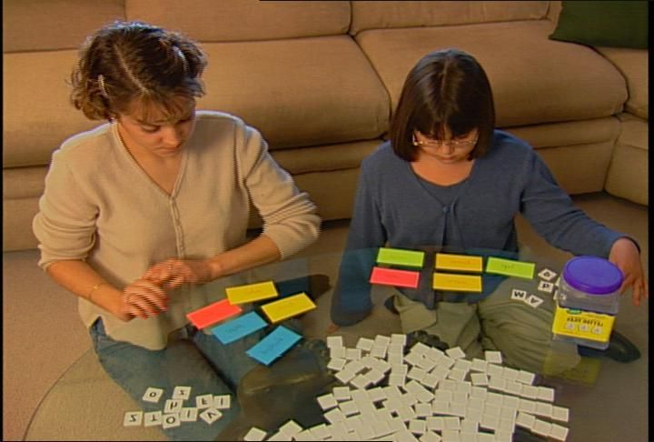 Two girls playing a Spelling Powwer reinforcement activity for spelling